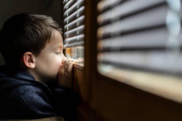 Small sad boy looking through the window during Coronavirus isolation. stock photo