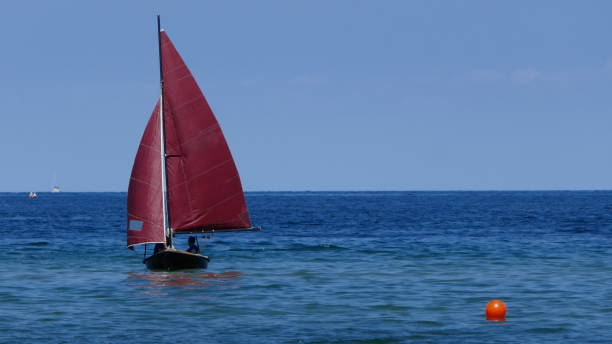 small sailboat, a sailing dinghy with dark red sails swims in the blue sea Old, small sailing boat with red sails sailing dinghy stock pictures, royalty-free photos & images