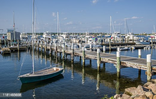 A small boat sits moored to a wooden pier on a calm summer evening in Rhode Island.
