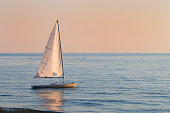 small sailboat in the water small sailboat in the water nex to the beach next to the beach in a summer sunset ready to sailing with the last breeze of the day
