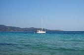 Small sailboat on a blue sea.