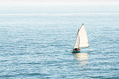 Small Sailboat in Open Sea on a Sunny Foggy Morning