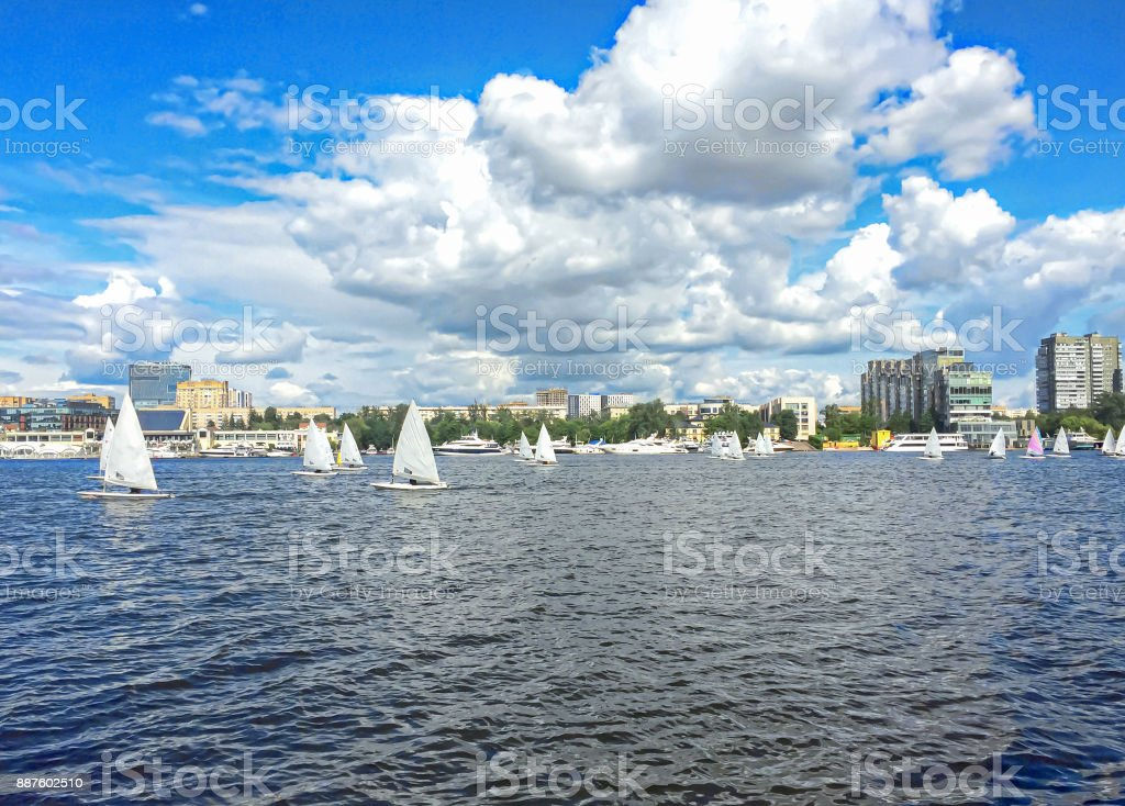 Small sailboats on the lake and big white cloud on blue sky stock photo