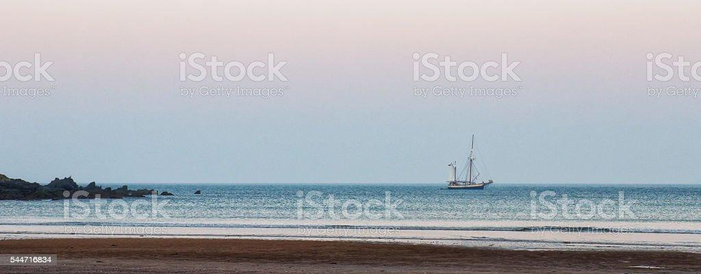 Small sailing boat anchored off shore stock photo