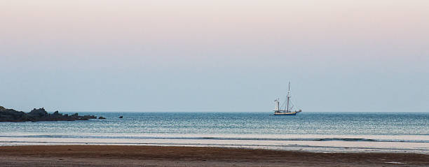 small sailing boat anchored off shore - rikmcrae stock photos and pictures