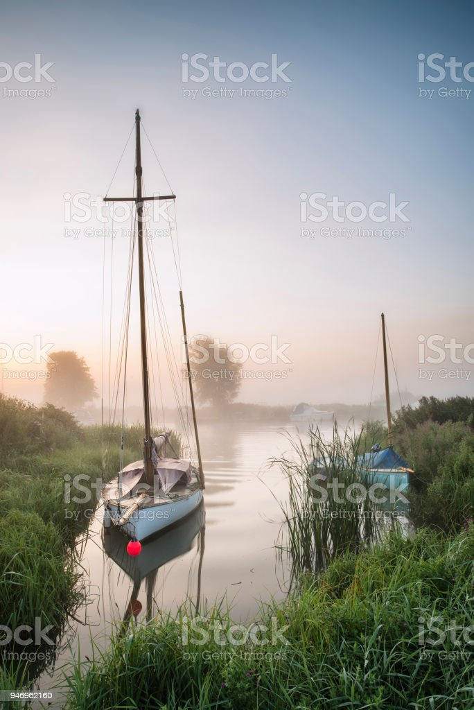 Small sailing boat moored on colorful River Thurne landscape during sunrise in Summer stock photo
