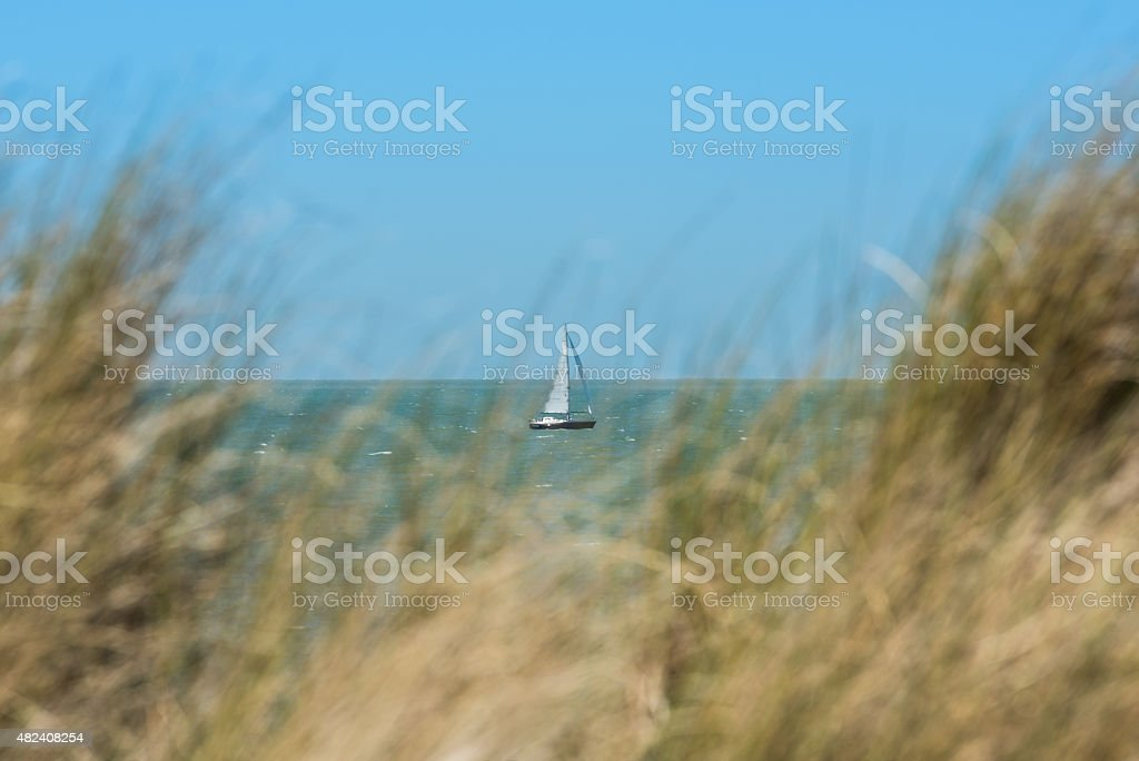 Small sailing ship, seen through high dune grass stock photo