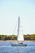 A small sailboat cruising along French Riviera coastline