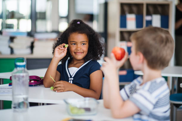 Small school children sitting at the desk in classroom, eating fruit. stock photo