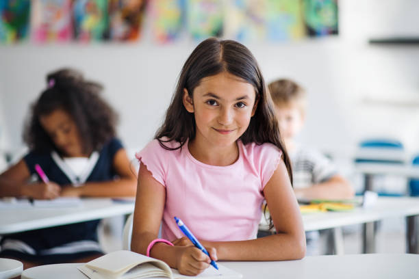 A small school girl sitting at the desk in classroom, looking at camera. stock photo