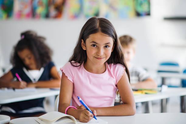 Ein kleines Schulmädchen, das am Schreibtisch im Klassenzimmer sitzt und in die Kamera schaut. – Foto