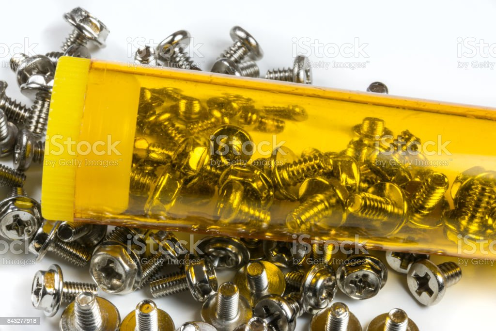 Small screws in yellow box on white background stock photo