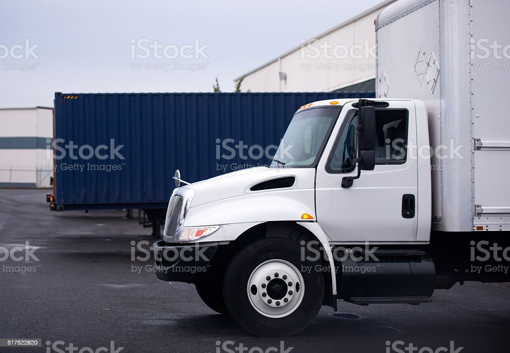 Small semi truck with box on warehouse parking lot stock photo