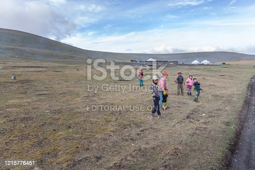 .Altai, Mongolia - June 14, 2017: Children welcome tourists traveling by car.