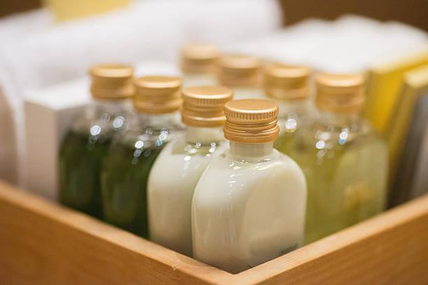 piccolo flaconi di shampoo wodden il cestello in camera - prodotto per l'igiene personale foto e immagini stock