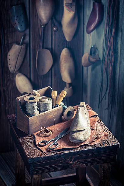 small shoemakers workshop with tools, shoes and leather - remmar godis bildbanksfoton och bilder
