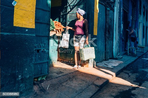 Havana, Cuba - March 19, 2015: Senior woman standing outside a small shop in Havana, Cuba. The client is buying carrots.
