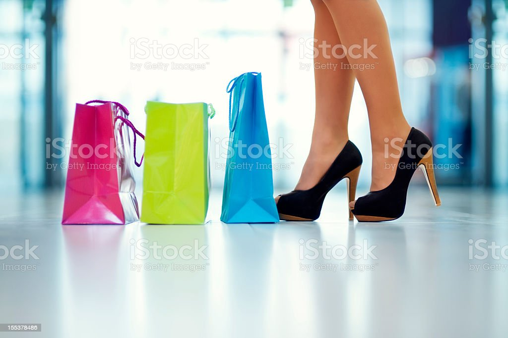 Small shopping bags and a woman in black heels royalty-free stock photo