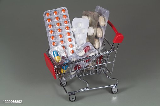 Small shopping cart and different packs of pills