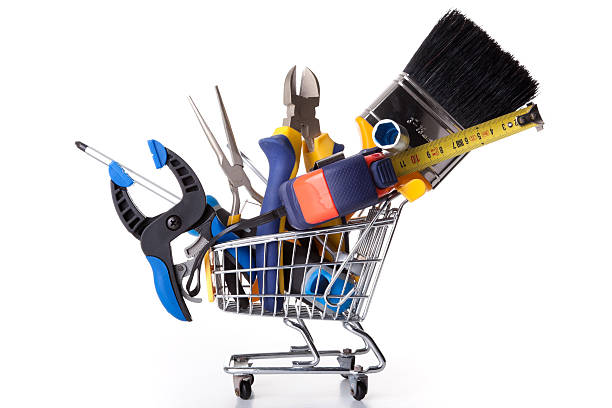 Small shopping cart containing oversized construction tools stock photo