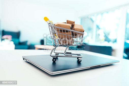 istock Small shopping cart with cardboard boxes on top of laptop 666069072