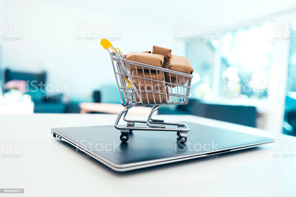 Small shopping cart with cardboard boxes on top of laptop stock photo