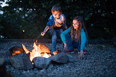 Happy little girl and her small brother enjoying by the campfire in the evening at the backyard. Copy space.