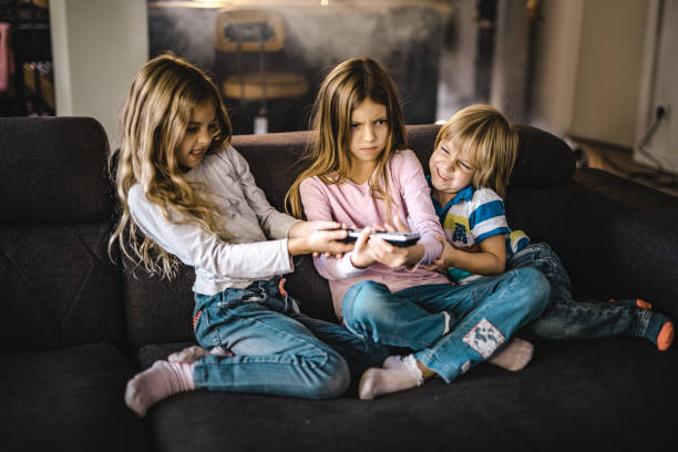 Small siblings fighting over a remote control in the living room. Angry little kids fighting over a remote control while watching TV on sofa at home. arguing stock pictures, royalty-free photos & images