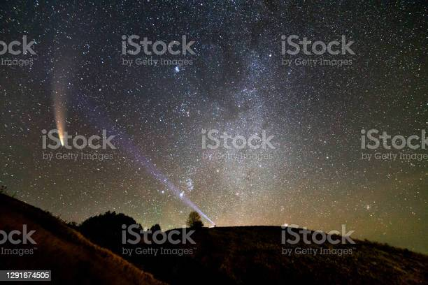 Photo of Small silhouette of a scientist with flashlight on his head pointing bright beam of light on starry sky with C/2020 F3 (NEOWISE) comet with light tail. Space exploration concept.