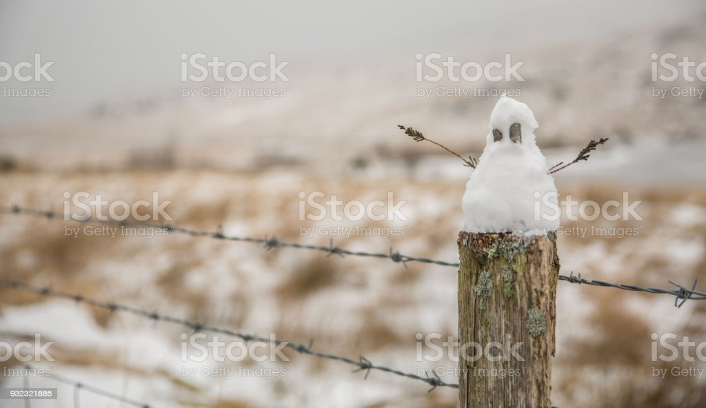Small snowman sitting on a fence post with stick arms. stock photo