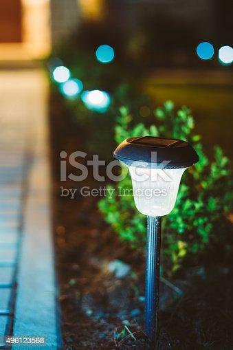 498598201 istock photo Small Solar Garden Light, Lantern In Flower Bed. Garden Design. 496123568
