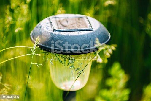 498598201 istock photo Small Solar Garden Light, Lantern In Flower Bed. Garden Design. 528500726