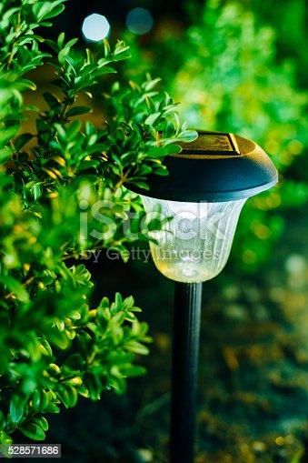 498598201 istock photo Small Solar Garden Light, Lantern In Flower Bed. Garden Design. 528571686
