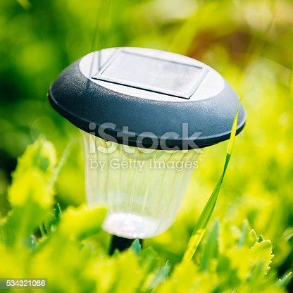 498598201 istock photo Small Solar Garden Light, Lantern In Flower Bed. Garden Design. 534321086