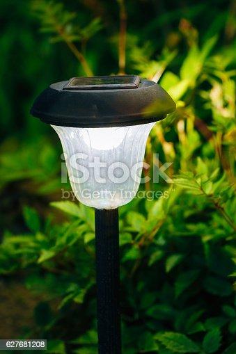498598201 istock photo Small Solar Garden Light, Lantern In Flower Bed. Garden Design. 627681208