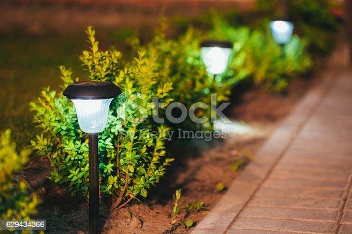 498598201 istock photo Small Solar Garden Light, Lantern In Flower Bed. Garden Design. 629434366