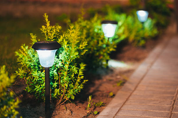 Small Solar Garden Light, Lantern In Flower Bed. Garden Design. Decorative Small Solar Garden Light, Lanterns In Flower Bed In Green Foliage. Garden Design. Solar Powered Lamps In Row grounds stock pictures, royalty-free photos & images