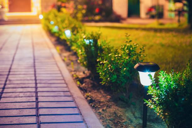 kleine solar garten licht, laterne im blumenbeet. garten-design. solar betriebene lampe - solarleuchten stock-fotos und bilder