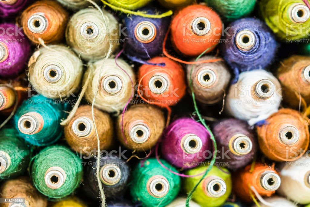 small spools of thread in many colors stock photo