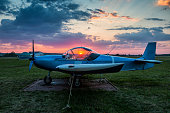 A small sports aircraft parked at the airfield at scenic sunset