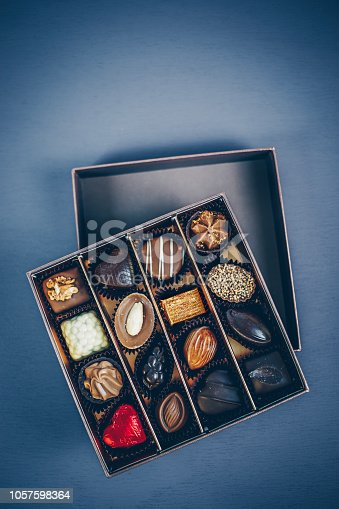 183269671istockphoto Small square box of chocolate pralines and truffles assorted. Different shapes and fillings. Blue toned background, directly above. 1057598364