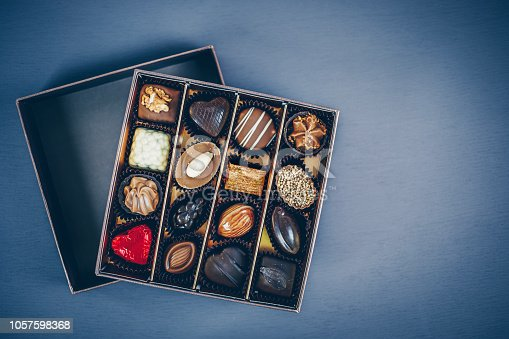 183269671istockphoto Small square box of chocolate pralines and truffles assorted. Different shapes and fillings. Blue toned background, directly above. 1057598368