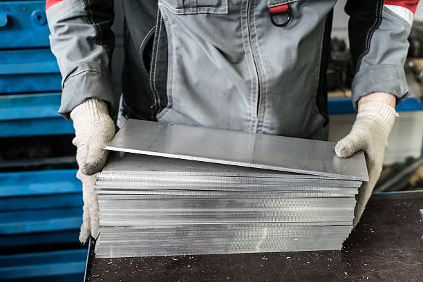 small stack of steel plates on the bench miller small stack of steel plates on the bench miller, hand in working glovessmall stack of steel plates on the bench miller, hand in working gloves sheet metal stock pictures, royalty-free photos & images