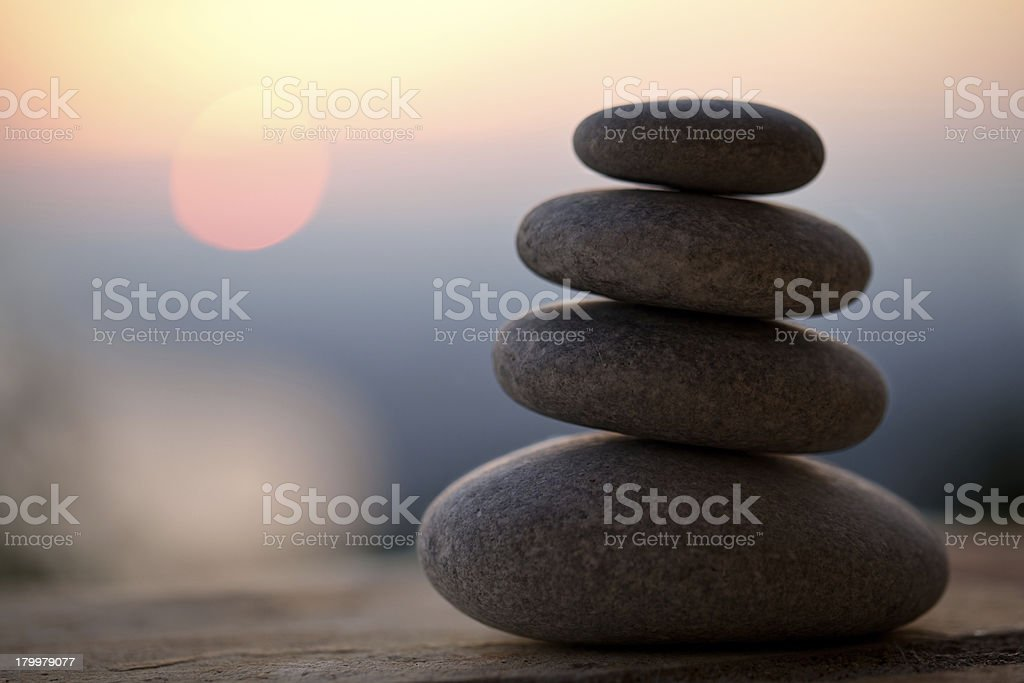 Small stack of stones on a blurred sunset background stock photo