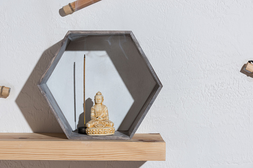 Small Statue Of Buddha In Frame On Wooden Shelf Stock Photo - Download Image Now