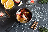 Small stewpot with mulled wine and cinnamon sticks, slice of oranges and apple on dark table top view. Hot winter drink. Christmas beverage.