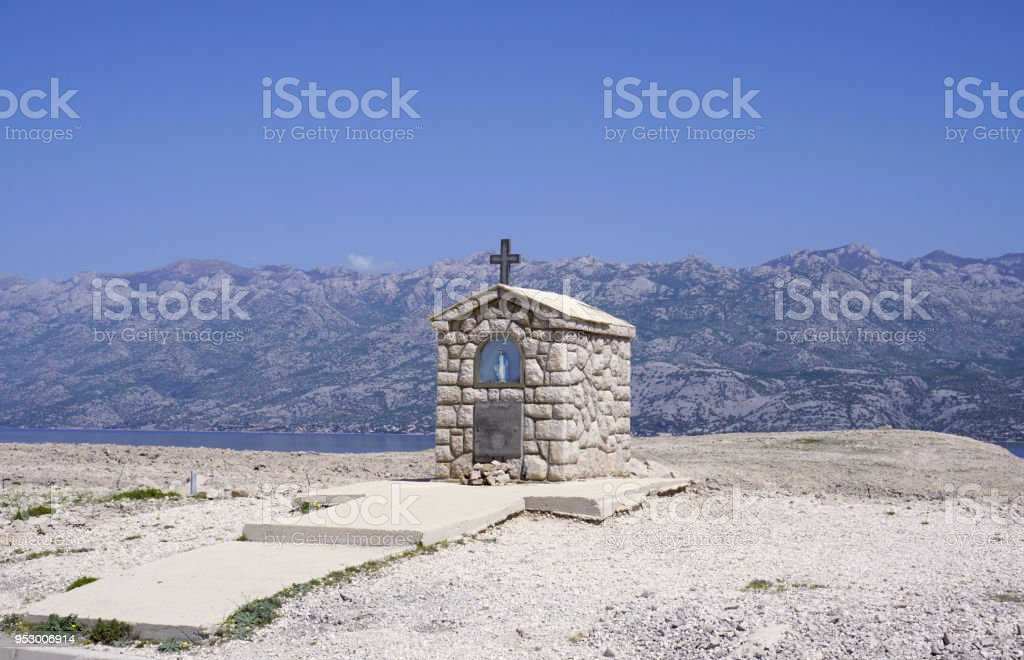 Small stone chapel with Mary statue in front of mountain Velebit in Croatia stock photo