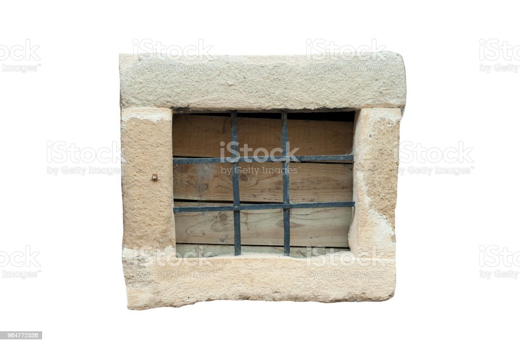 Small stone frame window with black metal bars isolated on white background. Vintage window. royalty-free stock photo