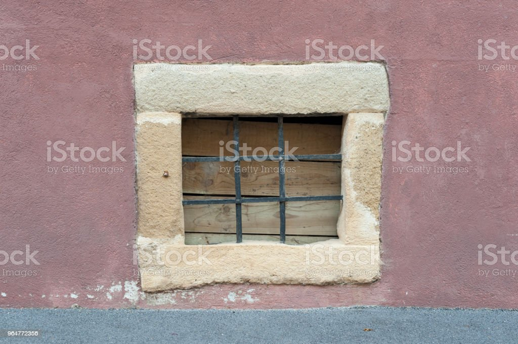 Small stone frame window with black metal bars on red wall. Vintage window royalty-free stock photo