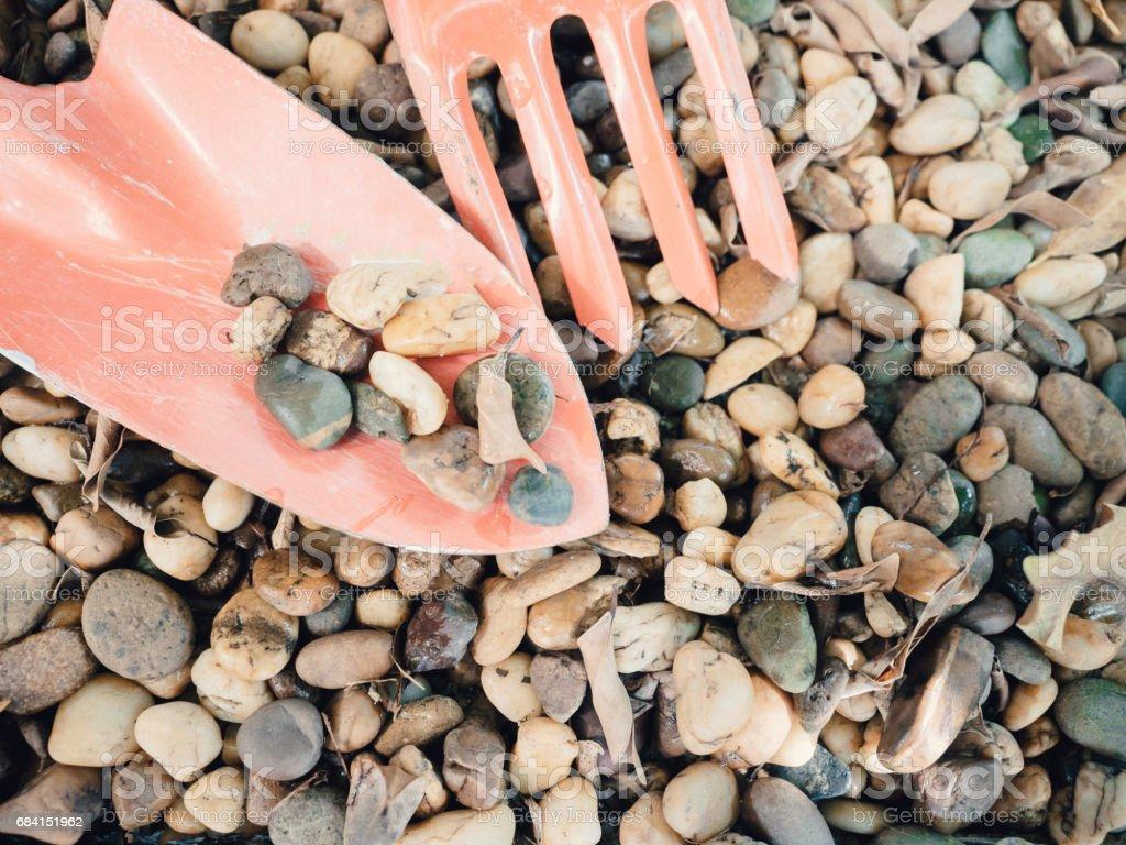 small stone on orange spade tool for gardening with copy space zbiór zdjęć royalty-free